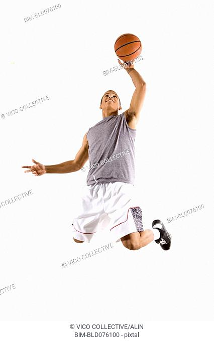 Mixed race basketball player jumping with ball