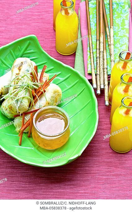 Egg rolls, chopsticks, lemonade bottles