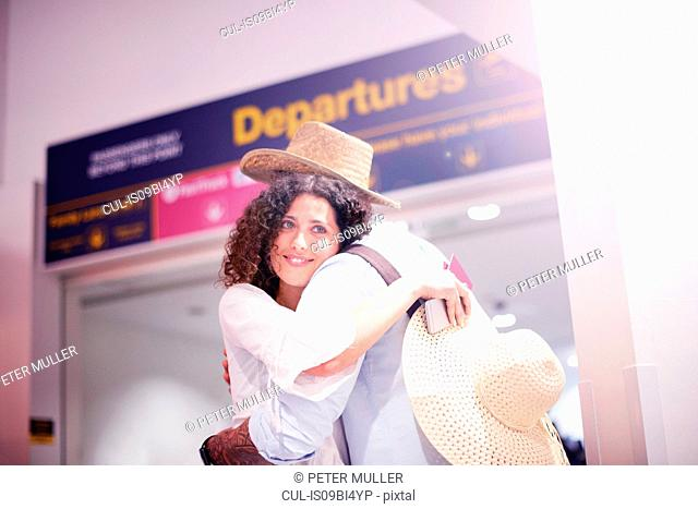Man and woman hugging at departure lounge of airport