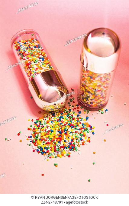 Concept of salt and pepper with bright and vibrant confetti on pink background