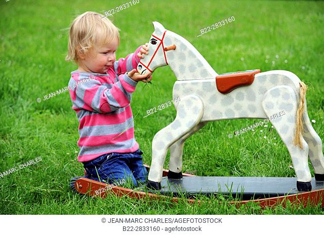 2 years old girl playing with a wooden horse