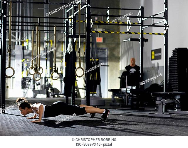 Woman in plank position in empty gym