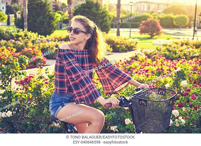 Teen girl riding bicycle in a city flowers park happy