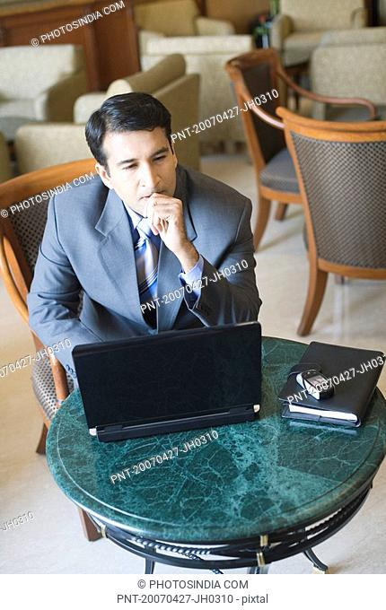High angle view of a businessman sitting in an armchair and thinking