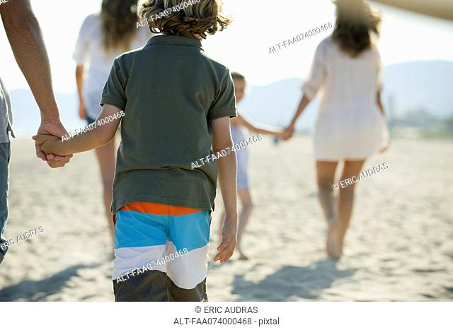 Boy at the beach with his family, holding father's hand, rear view