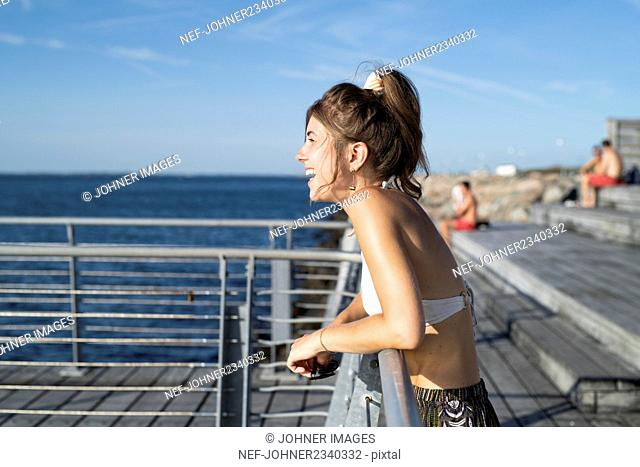 Young woman laughing on pier