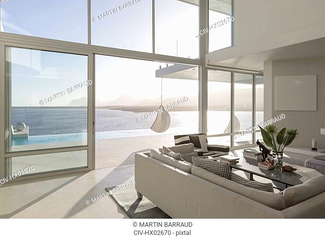 Sunny, tranquil modern luxury home showcase interior living room with ocean view