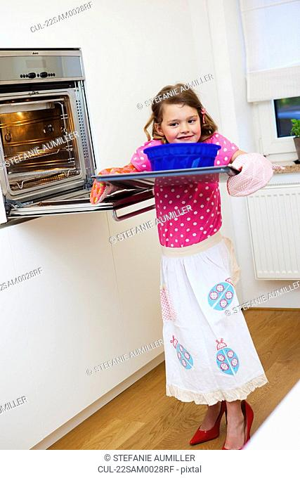 Girl taking a cake out of the oven