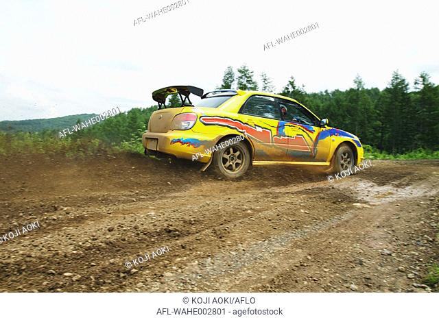 Rally car racing on dirt track