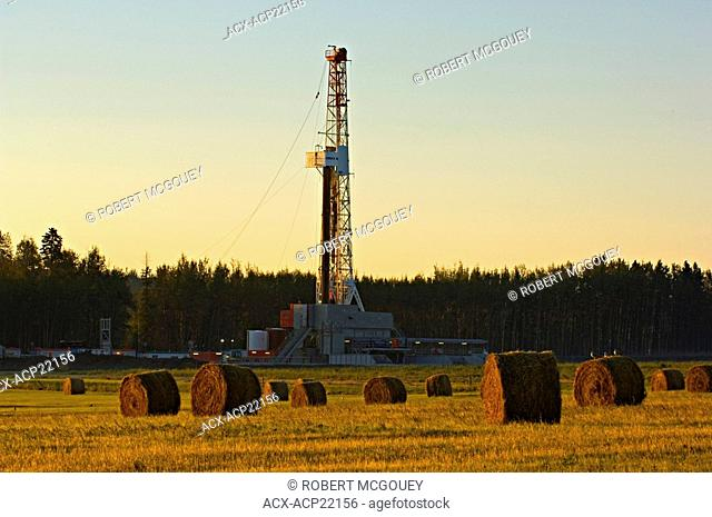 A land based drilling rig exploring for underground gas and oil in a farm field bathed in the warm morning sun light
