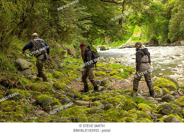 Caucasian friends walking in remote river