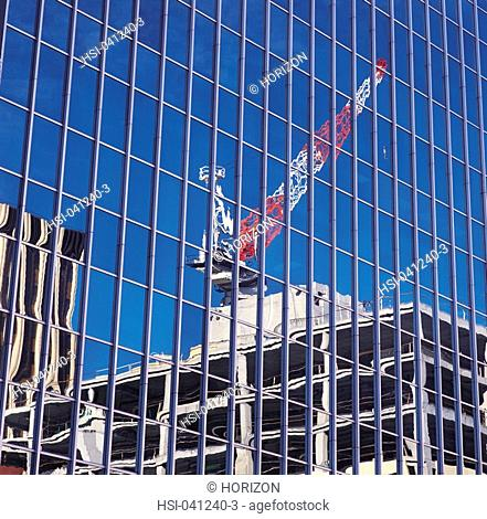 Reflection of crane in glass of building