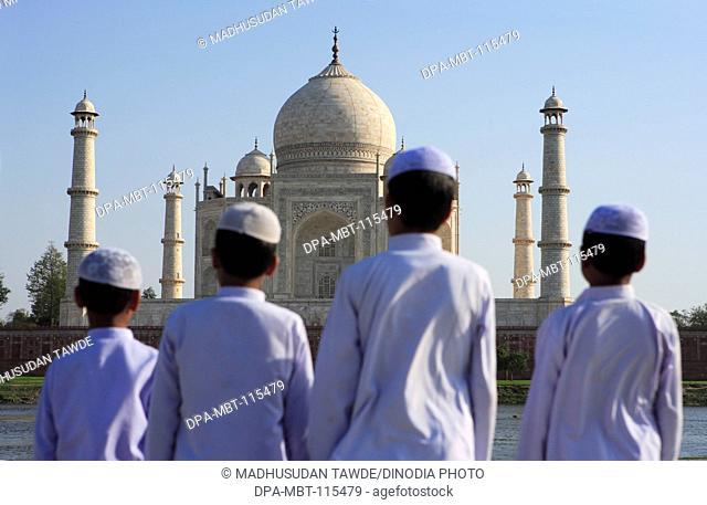 Young muslim boys performing religious prayer Namaz in front of Taj Mahal Seventh Wonders of World on south bank of Yamuna river , Agra , Uttar Pradesh