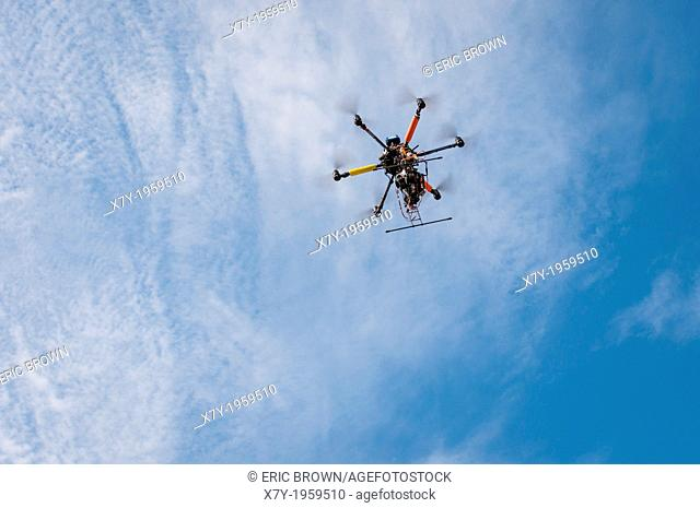 A drone with a camera hovers overhead in the sky