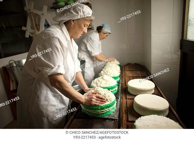 Women work making Pecorino cheese in Quesos Oliva artisanal cheese making workshop in Villaluenga del Rosario, Sierra de Grazalema Natural Park, Cadiz province