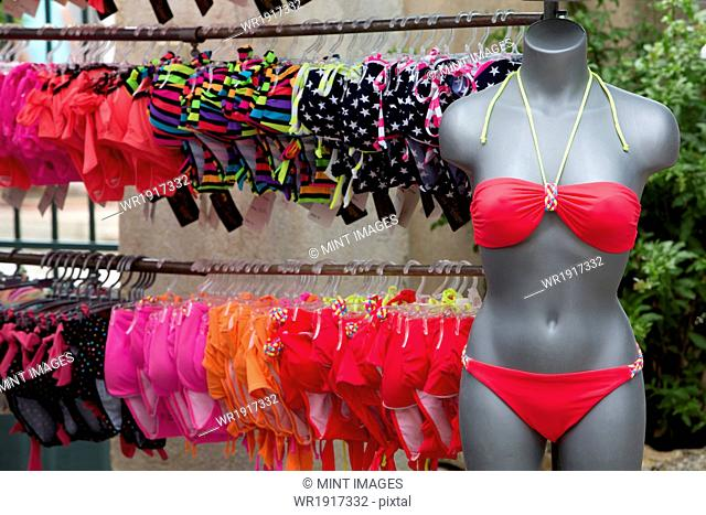 A clothes stall in the market, and a rack of women's swimwear. A pink bikini on a mannequin