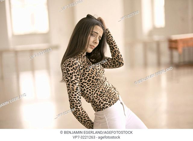 emotional woman dancing indoors, fashionable clothing style, flirty, in Munich, Germany