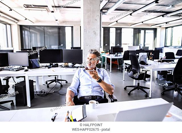 Mature businessman sitting at desk in office using smartphone