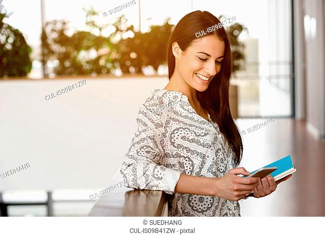 Young businesswoman in office corridor using smartphone touchscreen
