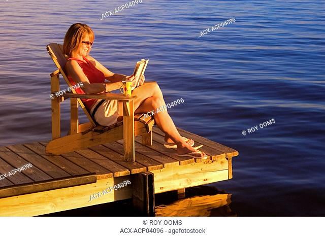 Canada, woman relaxing on dock at lake during sunset