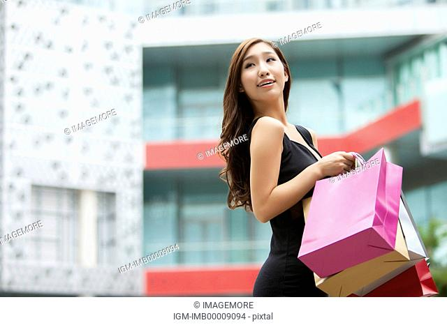 Young woman holding shopping bags and looking away with smile