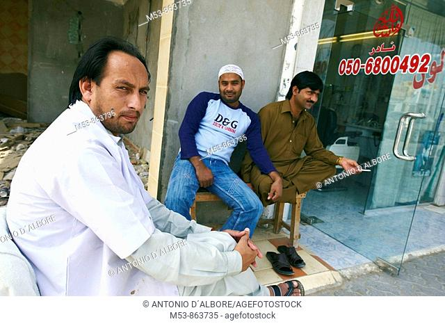 a pakistani barber wait for customer outside his shop in ras al-khaimah old town  ras al-khaimah  united arab emirates  middle east