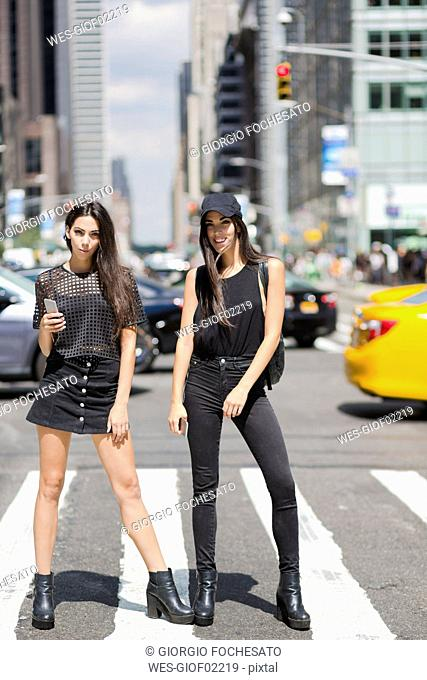 USA, New York City, two fashionable twin sisters standing on zebra crossing in Manhattan