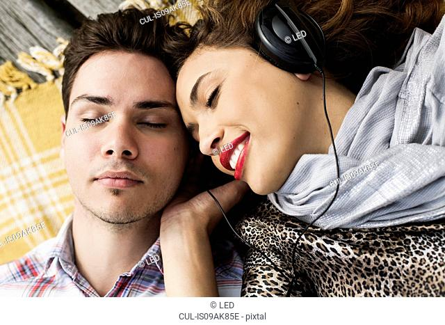 Overhead view of young couple listening to headphones with eyes closed on pier