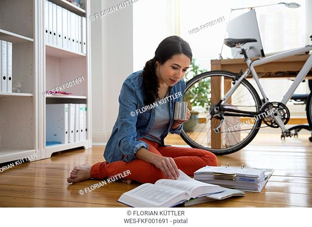 Woman sitting on the floor reading documents