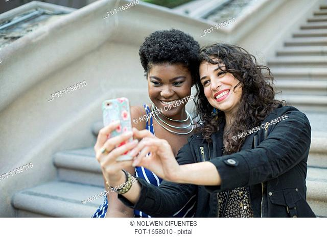 Happy woman taking selfie with young female friend against steps