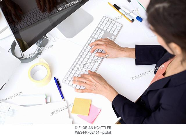 Woman using computer keyboard at desk in office
