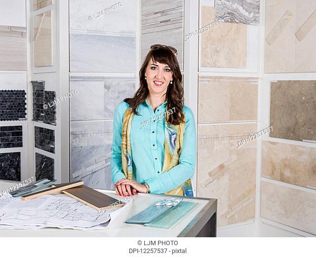 Interior designer selecting tiles in showroom of tile store; Edmonton, Alberta, Canada