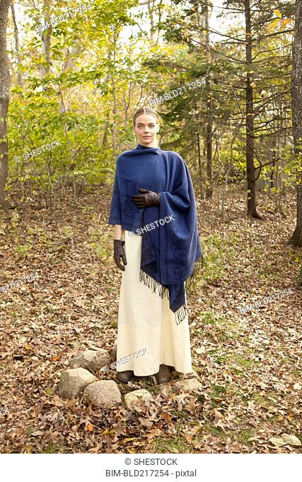 Woman wrapped in shawl in forest