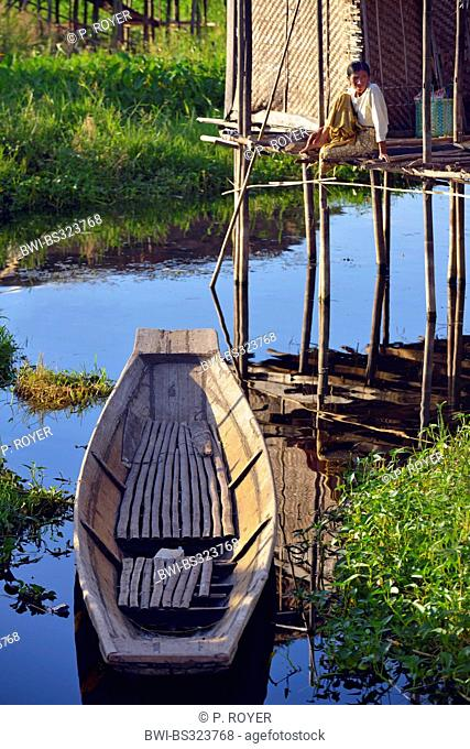 man sitting on the veranda of his house on one of the swimming islands on Inle Lake, Burma