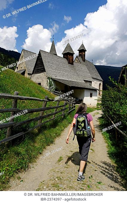 Hiker walking towards Bad Dreikirchen near Barbian, Eisack Valley, province of Bolzano-Bozen, Alto Adige, Italy, Europe