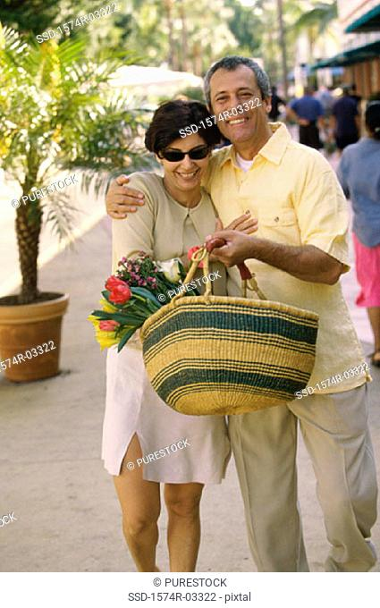 Mature couple walking on the street with a basket of flowers