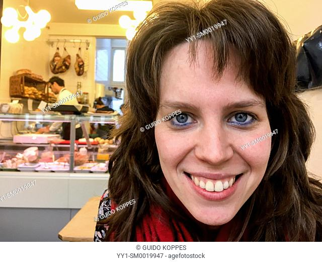 Tilburg, Netherlands. Young adult, caucasian woman with a big smile on her face, visiting a lunchroom to eat