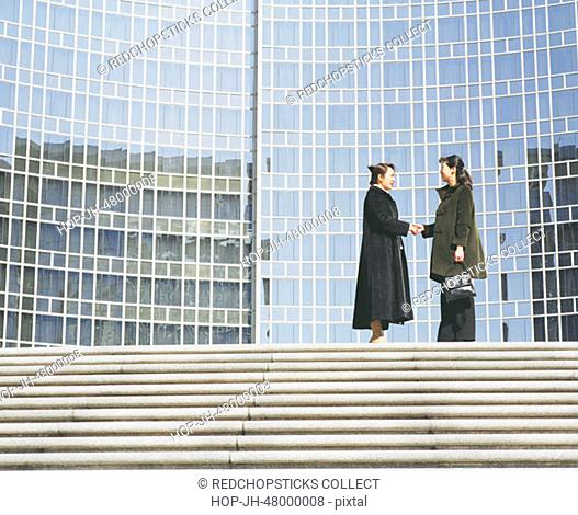 Side profile of two young women standing and shaking hands in front of a building