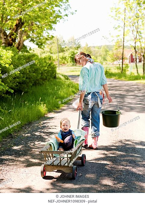 Mother pulling son in wagon