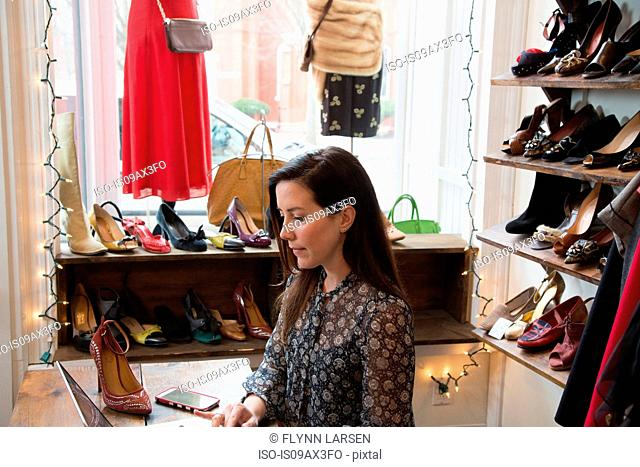 Businesswoman working at laptop in vintage shop