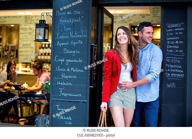Romantic couple leaving cafe