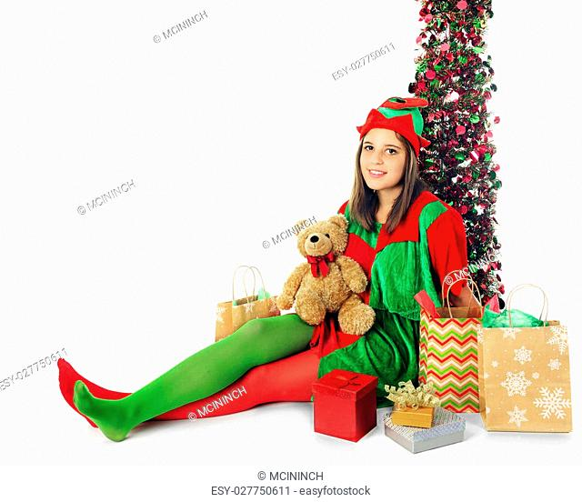 A pretty teen elf relaxed by a sparkly tree and surrounded by Christmas gifts. On a white background