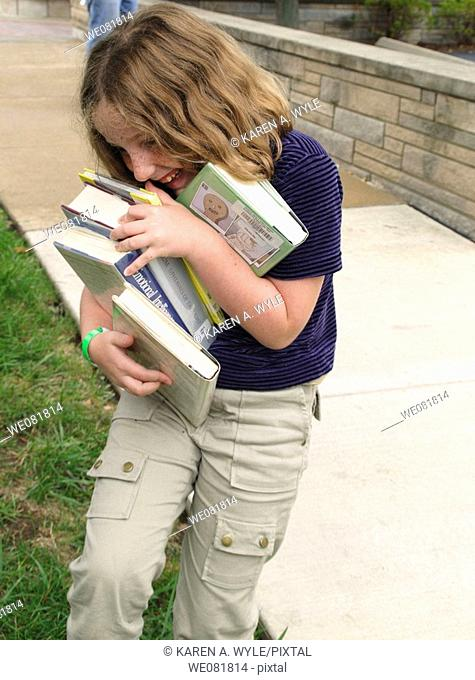 11-year-old girl holding too many library books, about to drop some, on street in Bloomington, Indiana, USA