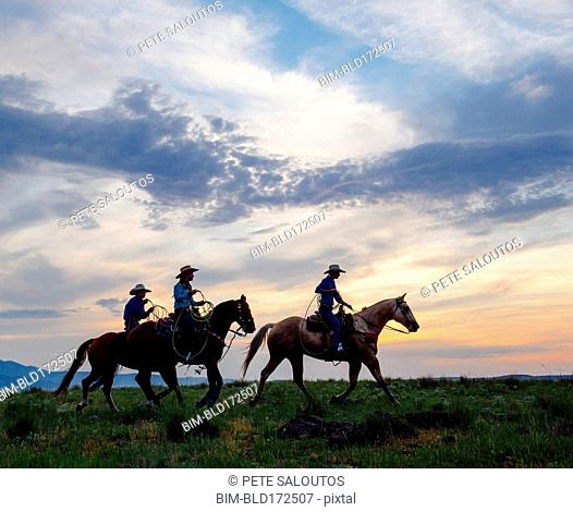 Cowgirls and cowboy riding horses in rural field