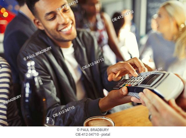 Smiling man paying bartender using credit card reader at bar