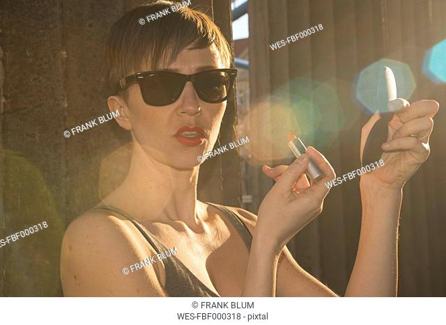 Germany, Berlin, portrait of woman with sunglasses putting lipstick on