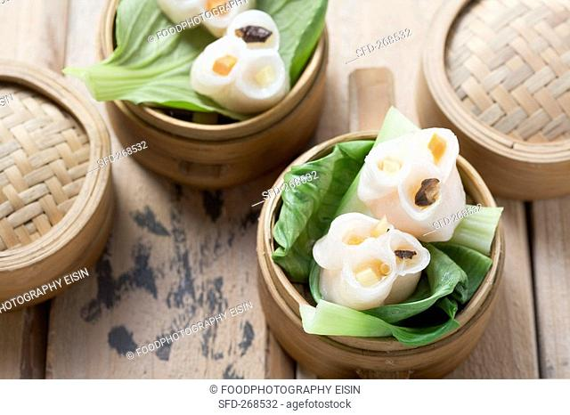 Dim sum on pak choi in bamboo steamers China