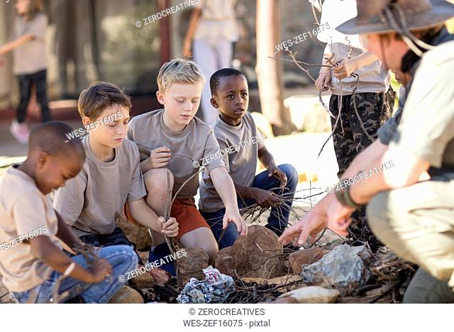 Children learning how to make a fire