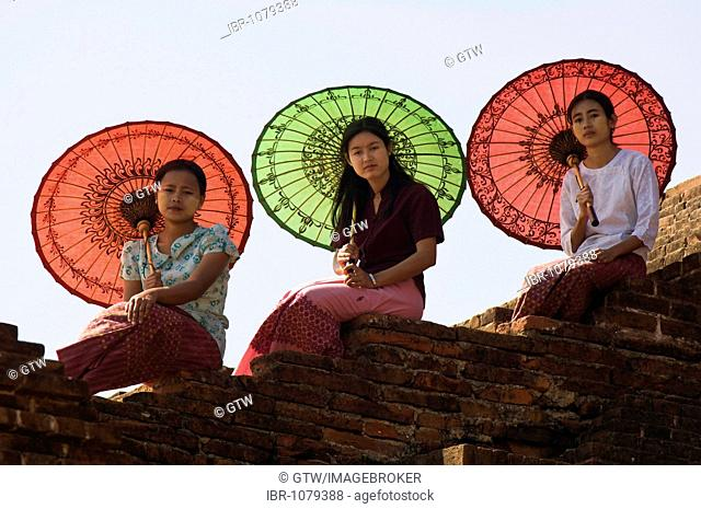 Young Burmese women with coloured parasols sitting on a temple wall, Bagan, Myanmar