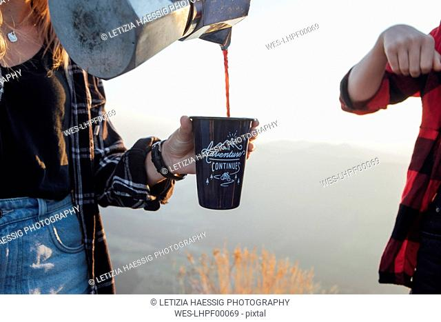 Close-up of woman on a hiking trip at sunrise pouring coffee into a cup for a friend